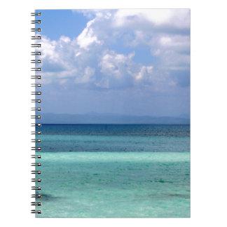 notebook with photo of Belize coastline