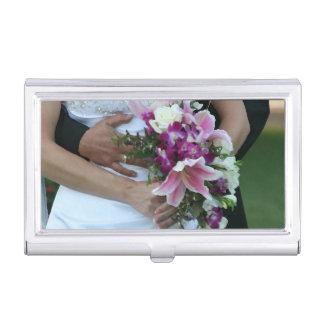 novia que detiene al novio de las flores detrás de cajas de tarjetas de presentación