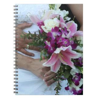 novia que detiene al novio de las flores detrás de cuadernos