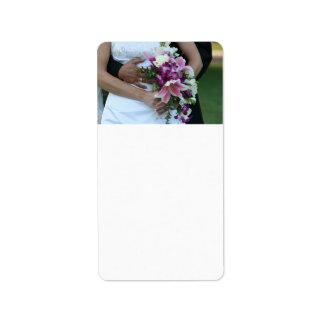 novia que detiene al novio de las flores detrás de etiqueta de dirección