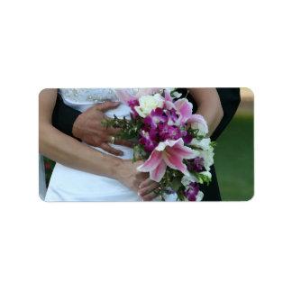 novia que detiene al novio de las flores detrás de etiquetas de dirección