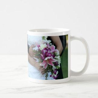 novia que detiene al novio de las flores detrás de taza básica blanca