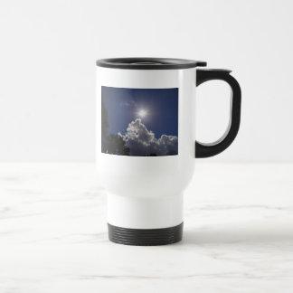 Nubes blancas mullidas del resplandor solar del taza de viaje