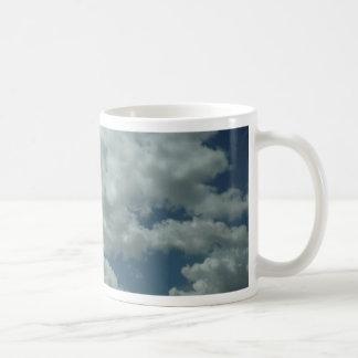 Nubes blancas, mullidas en cielo azul taza