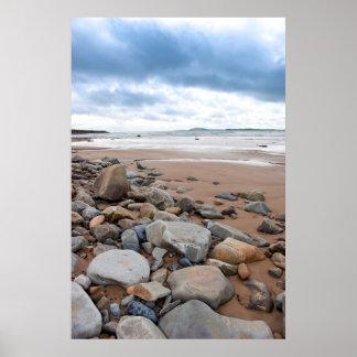 nubes de tormenta sobre la playa beal rocosa póster