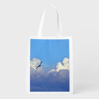 Nubes del balanceo con un vuelo del pájaro cerca bolsa para la compra