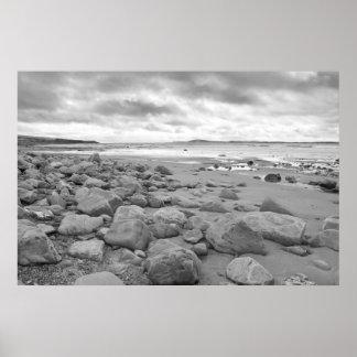 nubes tempestuosas sobre la playa beal rocosa póster