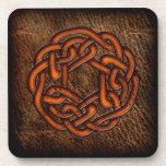 Nudo céltico anaranjado en el cuero posavasos de bebidas