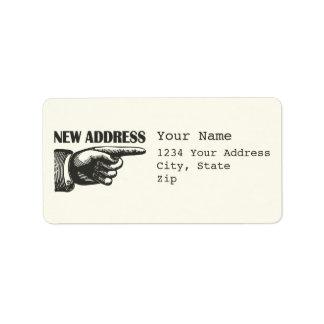 Nueva dirección que señala la mano etiquetas de dirección