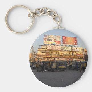 Number of parked auto rickshaws, shops and people basic round button keychain