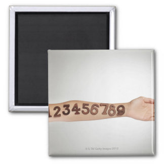 numbers affixed to the arm,ands close-up 2 inch square magnet
