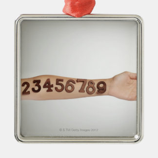 numbers affixed to the arm,ands close-up square metal christmas ornament