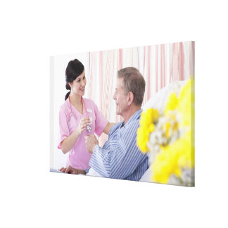 Nurse giving patient medication in hospital stretched canvas prints