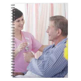 Nurse giving patient medication in hospital notebook