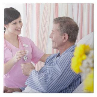 Nurse giving patient medication in hospital tile