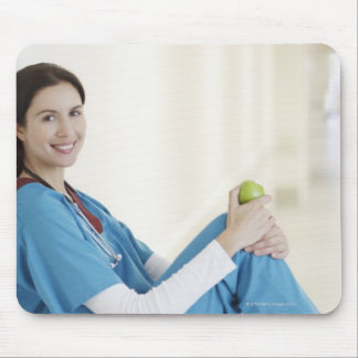 Nurse sitting with apple in hospital corridor mouse pad