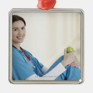 Nurse sitting with apple in hospital corridor christmas tree ornament