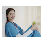 Nurse sitting with apple in hospital corridor poster