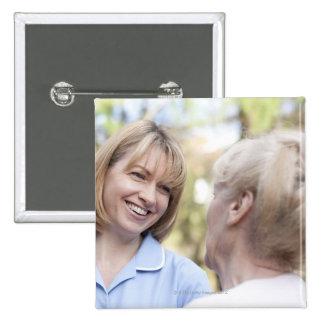 Nurse smiling and talking to a senior woman button