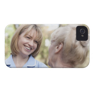 Nurse smiling and talking to a senior woman iPhone 4 case