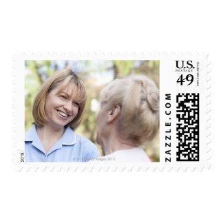 Nurse smiling and talking to a senior woman postage