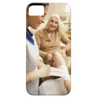 Nurse wrapping bandage on senior woman's leg to iPhone SE/5/5s case