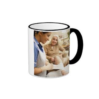 Nurse wrapping bandage on senior woman's leg to ringer coffee mug