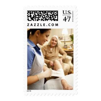 Nurse wrapping bandage on senior woman's leg to postage stamp