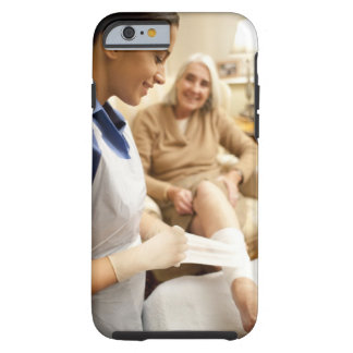 Nurse wrapping bandage on senior woman's leg to tough iPhone 6 case