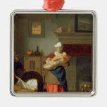 Nursemaid con el bebé en un interior adorno navideño cuadrado de metal