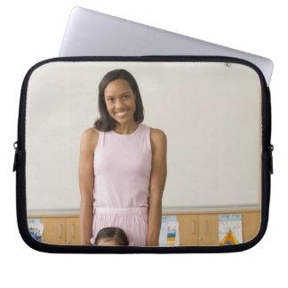 Nursery teacher by girl (3-5) with painting, computer sleeve