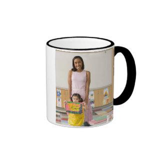 Nursery teacher by girl (3-5) with painting, ringer mug