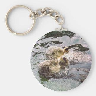 Nutrias de mar que llevan a cabo las manos llavero redondo tipo pin