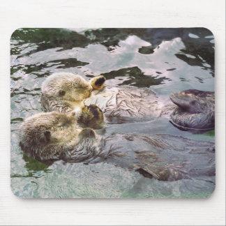 Nutrias de mar que llevan a cabo las manos tapete de ratón