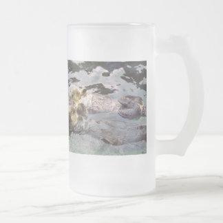 Nutrias de mar que llevan a cabo las manos tazas de café