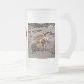 Nutrias de mar que llevan a cabo las manos taza de cristal