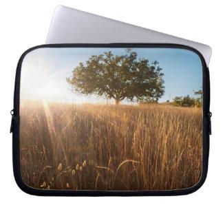 Oak tree in sunny golden meadow laptop sleeves