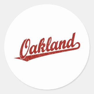 Oakland script logo in red distressed classic round sticker