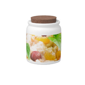 Oatmeal with raisins and berries in a wooden bowl candy jar