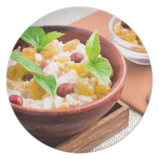 Oatmeal with raisins and berries in a wooden bowl melamine plate