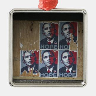 Obama firma adentro una ventana subida de un adorno navideño cuadrado de metal