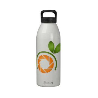 Obturador de la fotografía con las hojas verdes botella de beber