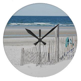 Ocean beach with beach fence large clock