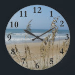 """Ocean Waves and Sand Dune Sea Oats Landscape Photo Large Clock<br><div class=""""desc"""">Ocean Waves and Sand Dune Sea Oats Landscape Photo Clock. This coastal landscape shows a close up of sea oats blowing in the wind, with the ocean waves and a sandy beach in background on a clear day with a blue summer sky. Sea Oats help preserve and protect sand dunes...</div>"""