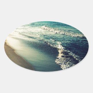 Océano y playa en la oscuridad pegatina ovalada
