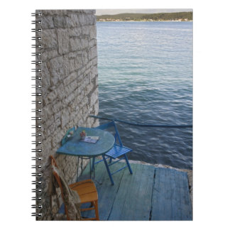Oceanside seating for two at tiny outdoor cafe, notebook