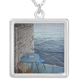 Oceanside seating for two at tiny outdoor cafe, square pendant necklace