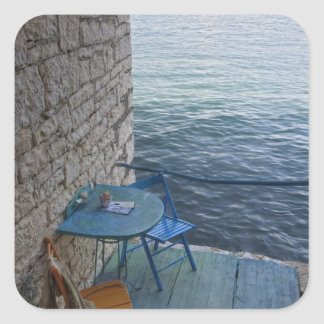 Oceanside seating for two at tiny outdoor cafe, square sticker