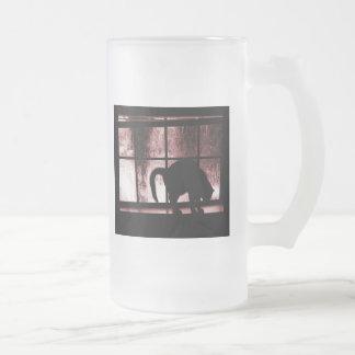 Octubre riega la silueta del gato en el rojo de la taza de cristal