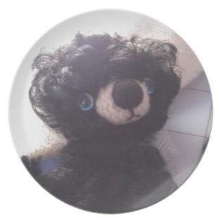ojos azules del mini de peluche negro del oso plato de cena